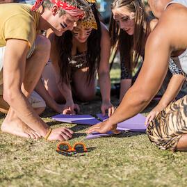 Survivor Team Solving Tangram Puzzle by the beach